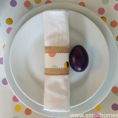 Easter table decorations with burlap ribbon wrapped around a cloth napkin.