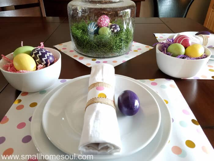 Easter table decorations looking at glass centerpiece.