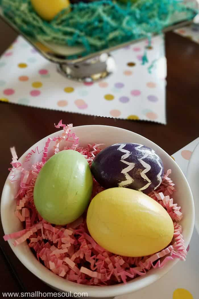 Easter table decorations with colorful eggs in a bowl with pink paper grass.