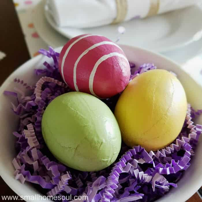 Easter table decorations with colorful eggs in a bowl with purple paper grass.