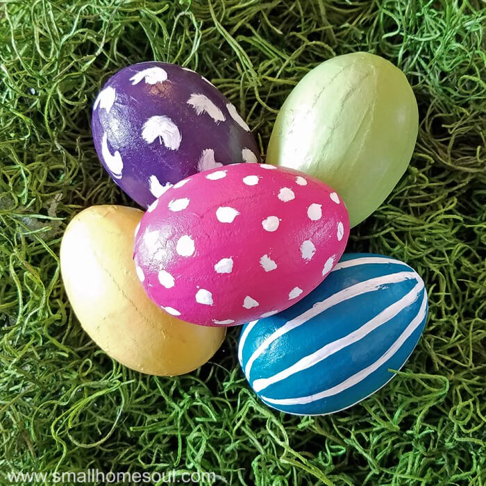 Completed painted easter eggs in purple pink teal yellow green on green moss.