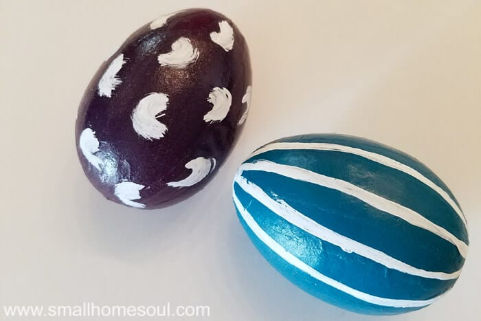 Grouping of cute and easy painted Easter eggs in purple and teal with strips and swipes painted on.