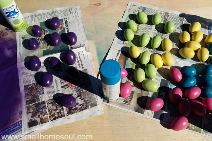 Spray painted eggs on newspaper in purple green, yellow, pink and teal.