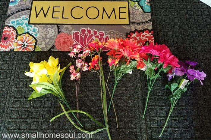 Fake flowers on doormat choosing bouquet for diy welcome sign.