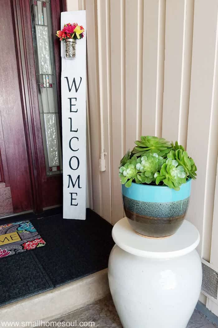 I love the flower vase in this DIY Welcome Sign, so pretty for your front porch.