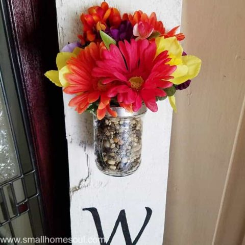 Colorful bouquet at top of diy welcome sign.