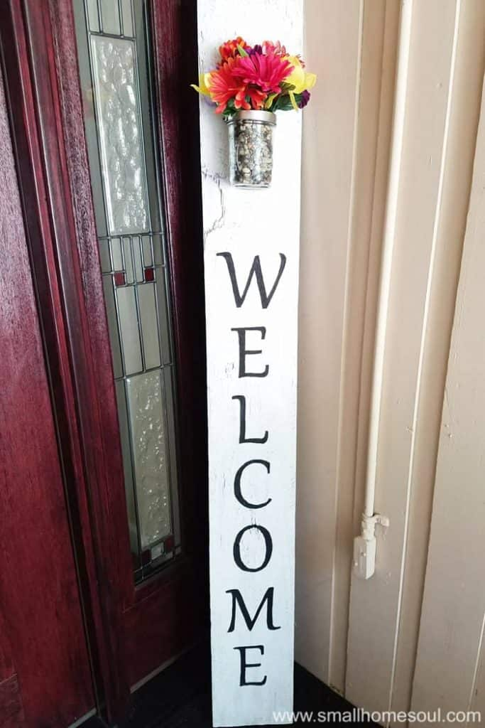 DIY welcome sign propped in corner of porch by front door.