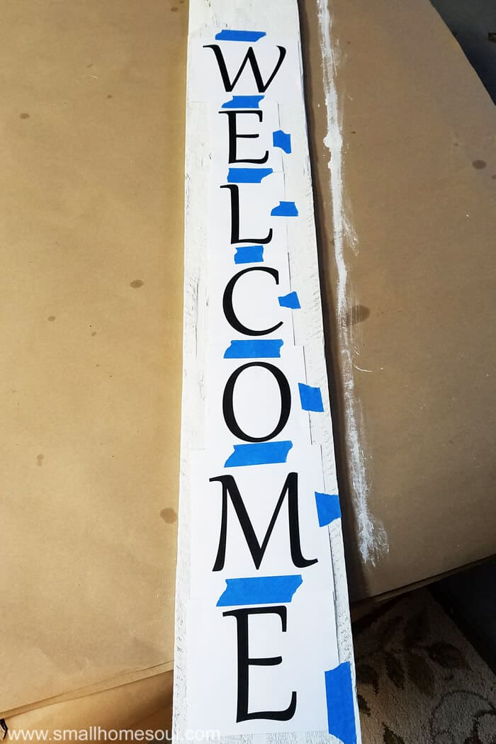 Letters for DIY Welcome Sign taped to painted fence board.