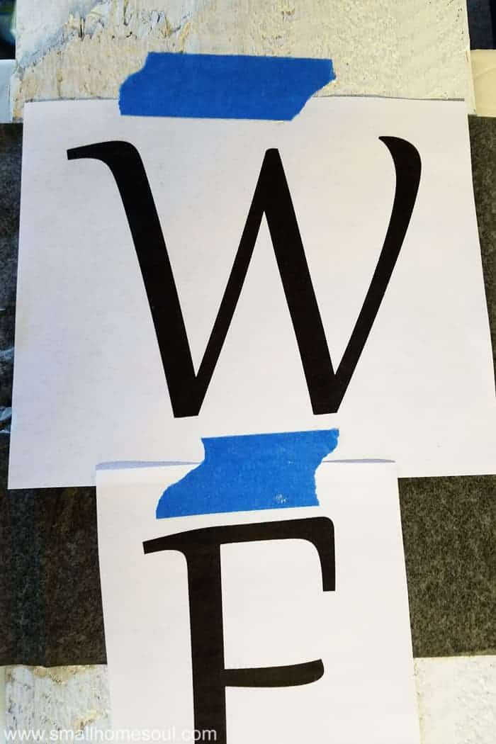 Taping letters together on diy welcome sign to get traced.