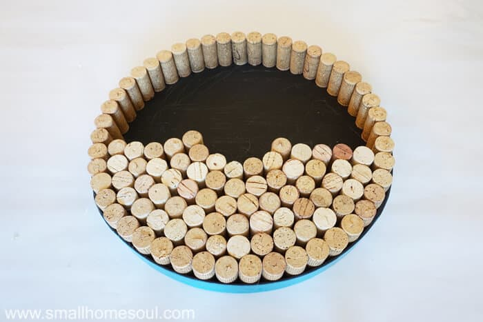 Gluing more corks into lid for DIY wine cork board.
