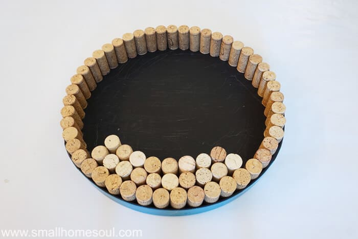 Gluing corks in circle for of lid wine cork board.
