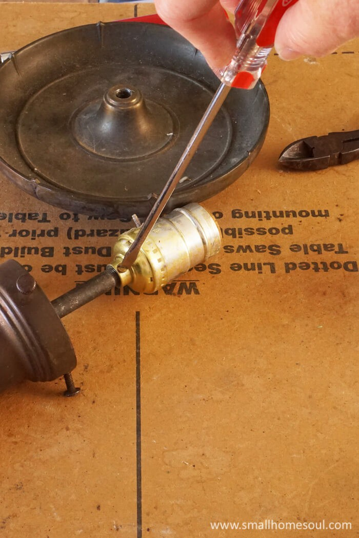 Remove the old lighting wire from the brass lamp base.