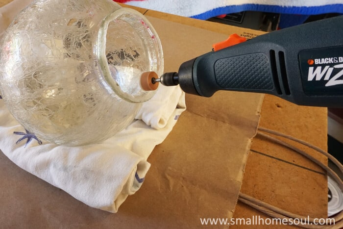 A rotary tool sands the glass globe for the brass lamp.