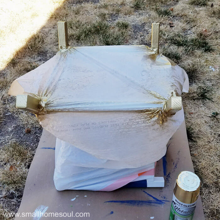 Dip the legs of the folding stool with gold spraypaint.