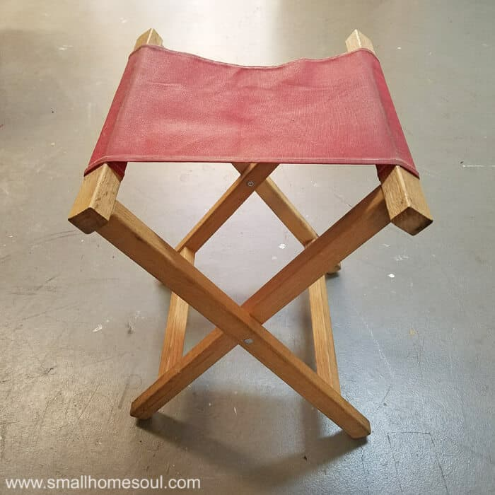Folding stool with red seat ready for a makeover.