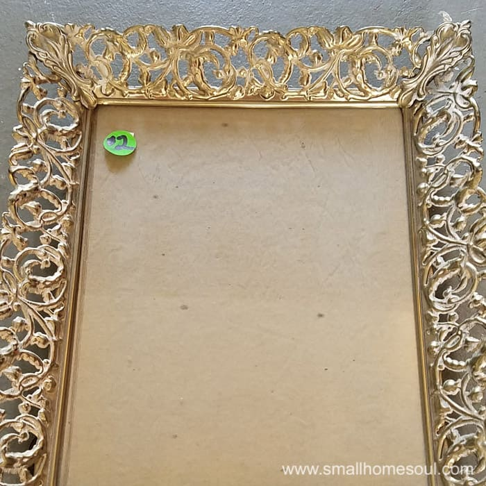 Old metal picture frame with no picture and a $2 green pricetag.