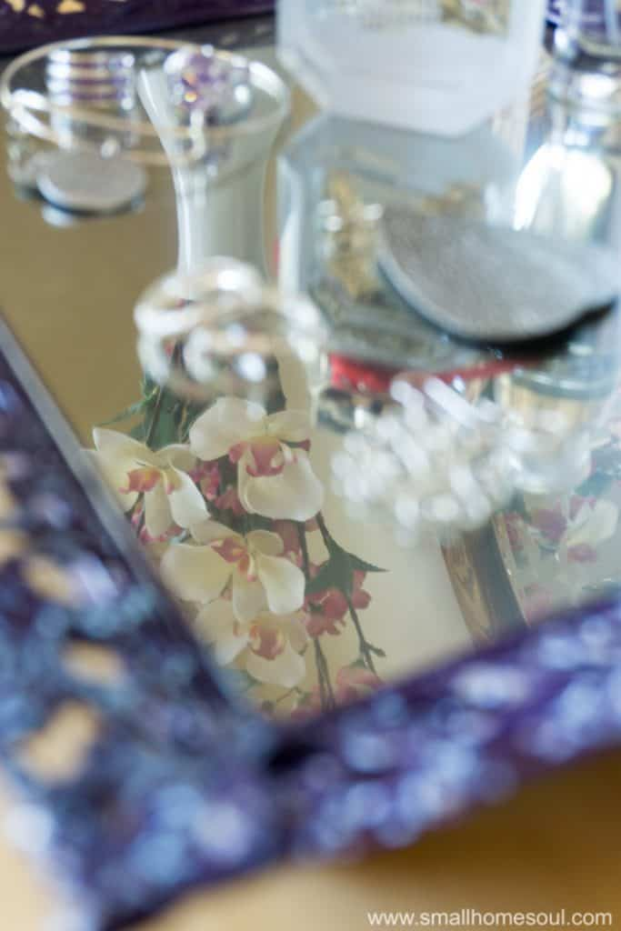Mirrored finish on the jewelry tray reflects flower from a vase.