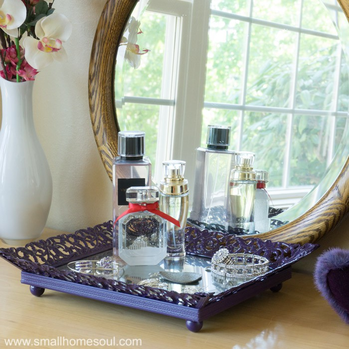 Jewelry tray on dresser reflected in mirror.