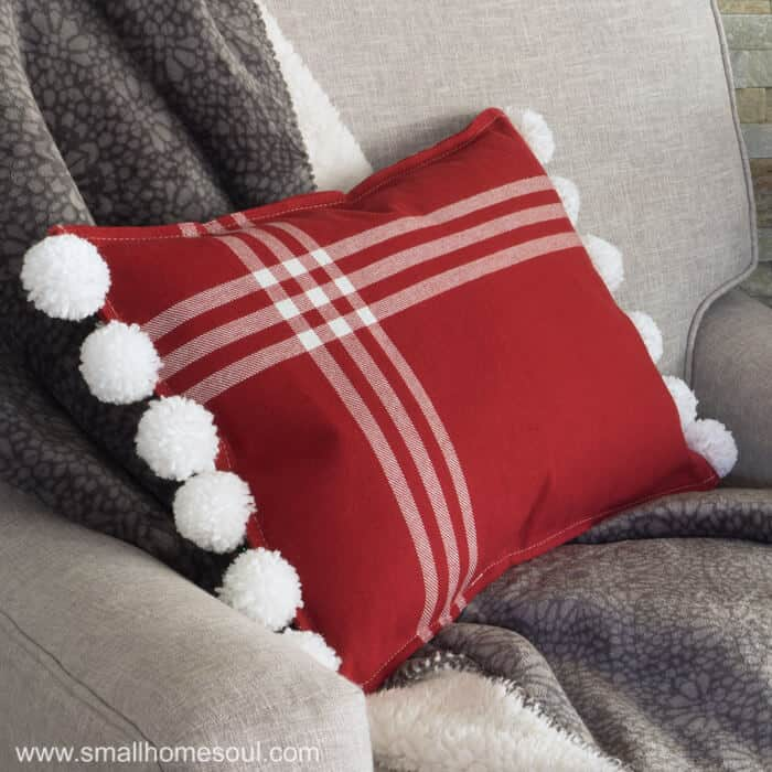 Finished Christmas Pom Pom Pillow in chair with throw.
