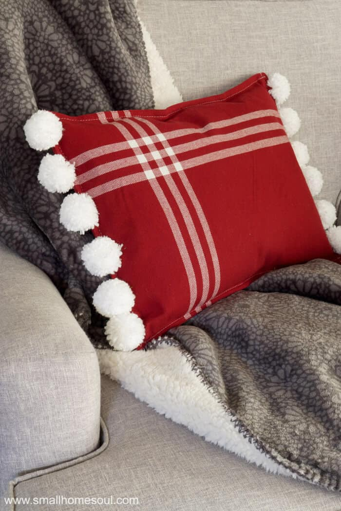 Christmas Pom Pom pillow looking pretty in my chair.