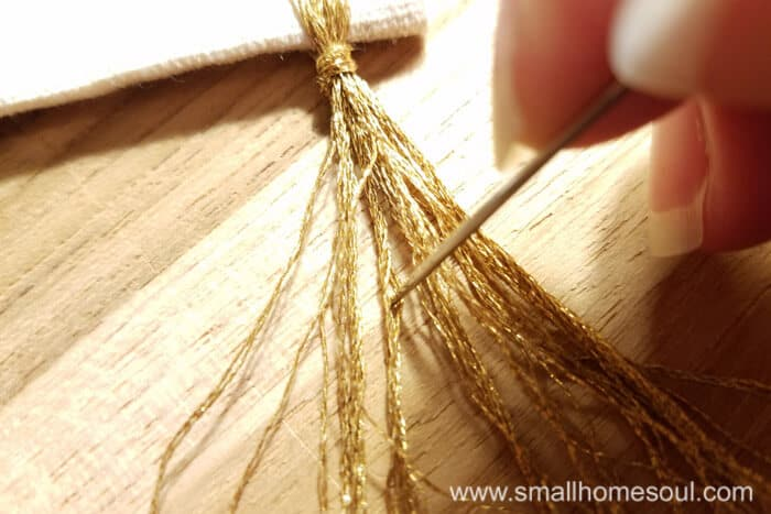 Separating floss threads on the grateful wall hanging.