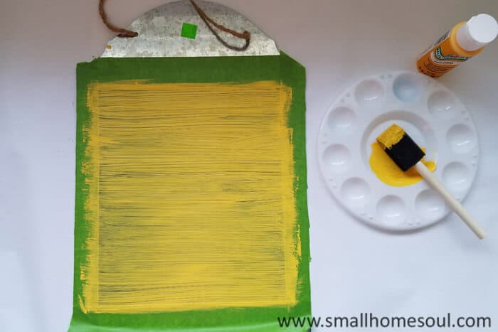 Painting the magnetic memo board a bright yellow.