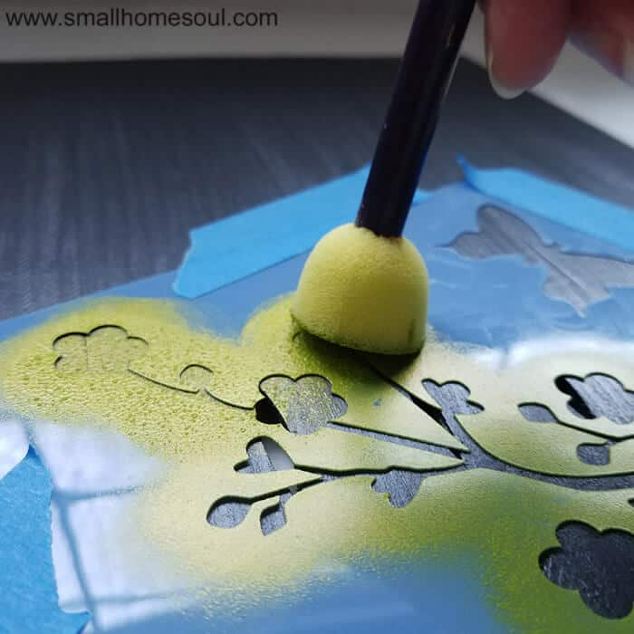 Stenciling the paint stick photo frame craft with shimmery green paint.