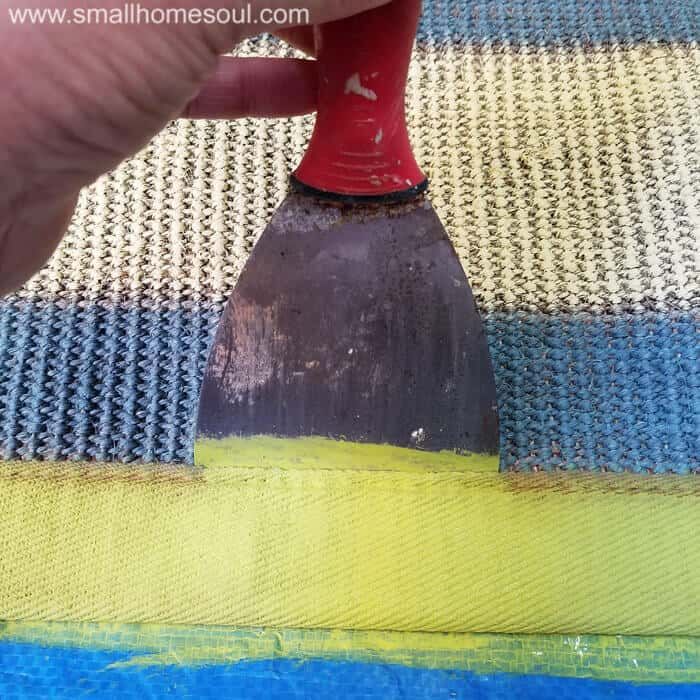 A putty knife helps paint a rug border.