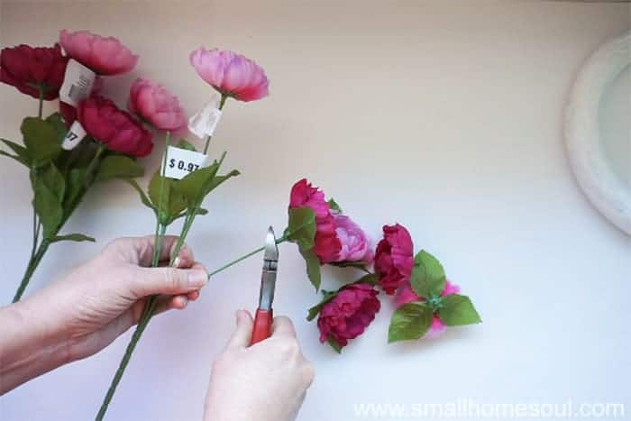 Cutting faux flowers off wire stems with wire cutters.