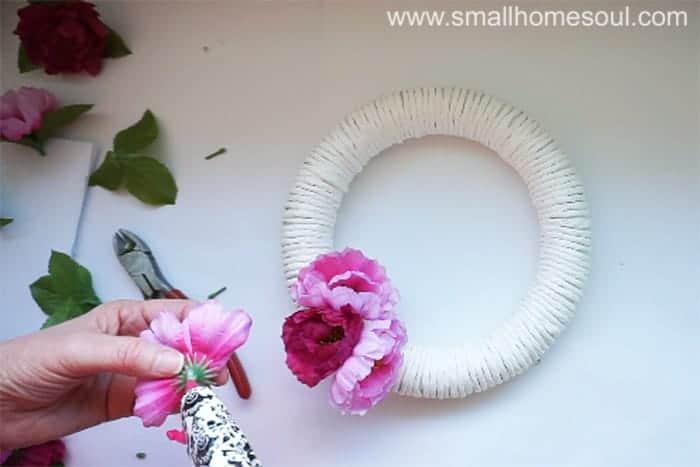 Hot glue flowers onto diy spring wreath.