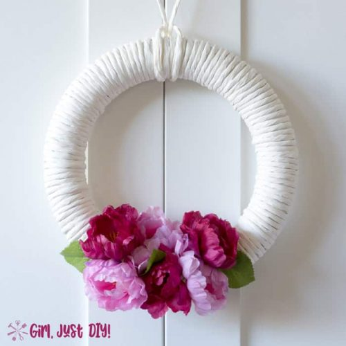 light and dark pink flowers on white wreath hanging from white door.