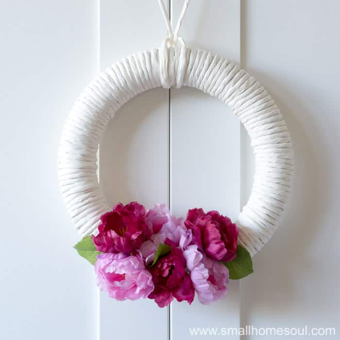 DIY Spring Wreath hanging on cabinet doors. White wreath with dark and light pink flowers and green leaves.