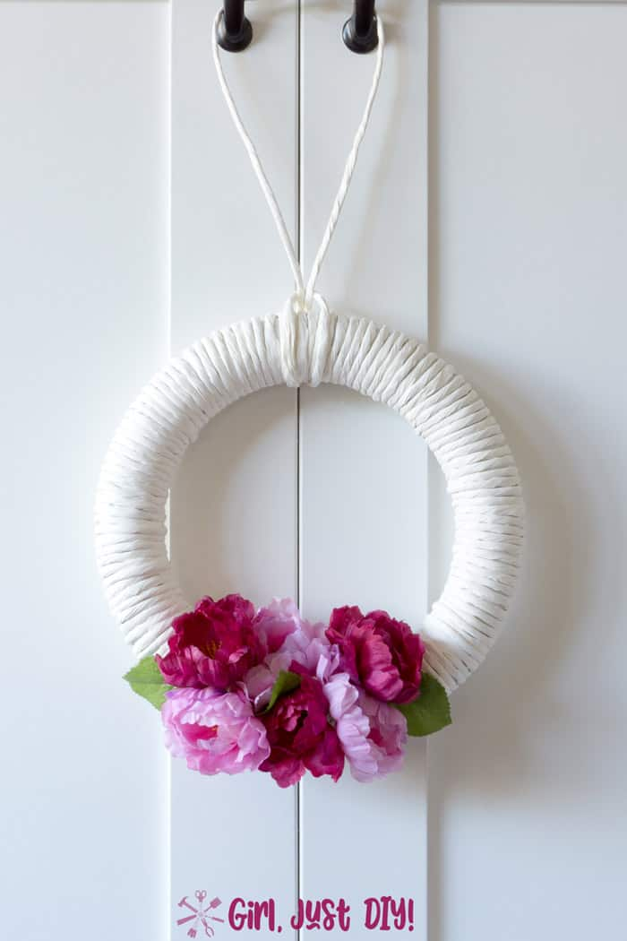 white wreath with dark and light pink flowers hanging on white door.