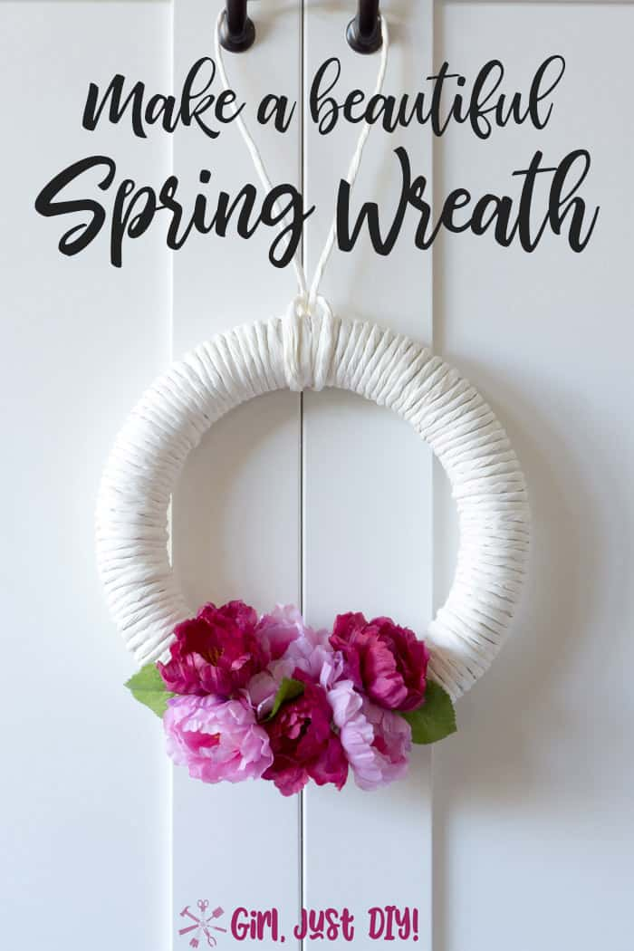 white wreath with dark and light pink flowers hanging on a white door.