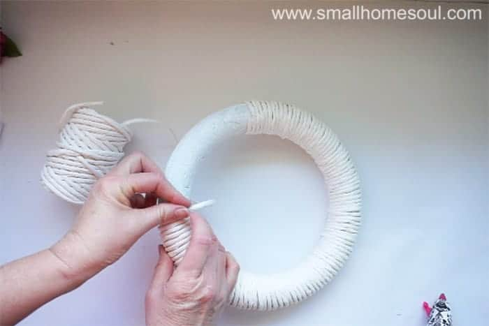 Wrapping paper twist ribbon around white painted wreath form.