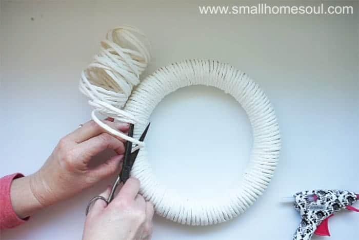 Cutting and gluing paper twist onto diy spring wreath.