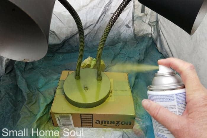 Applying green spray paint for desk lamp makeover.