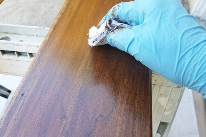 Wiping excess stain from floating wood shelves.