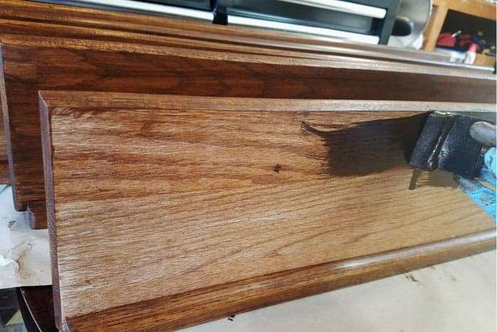 Staining backs of floating wood shelves.