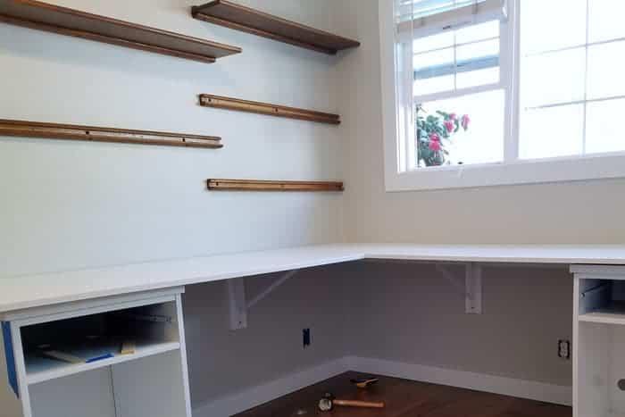 Installed floating wood shelves over desk.