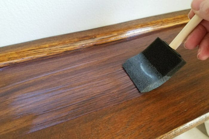 Top coating the floating wood shelves with sealer using a foam brush.