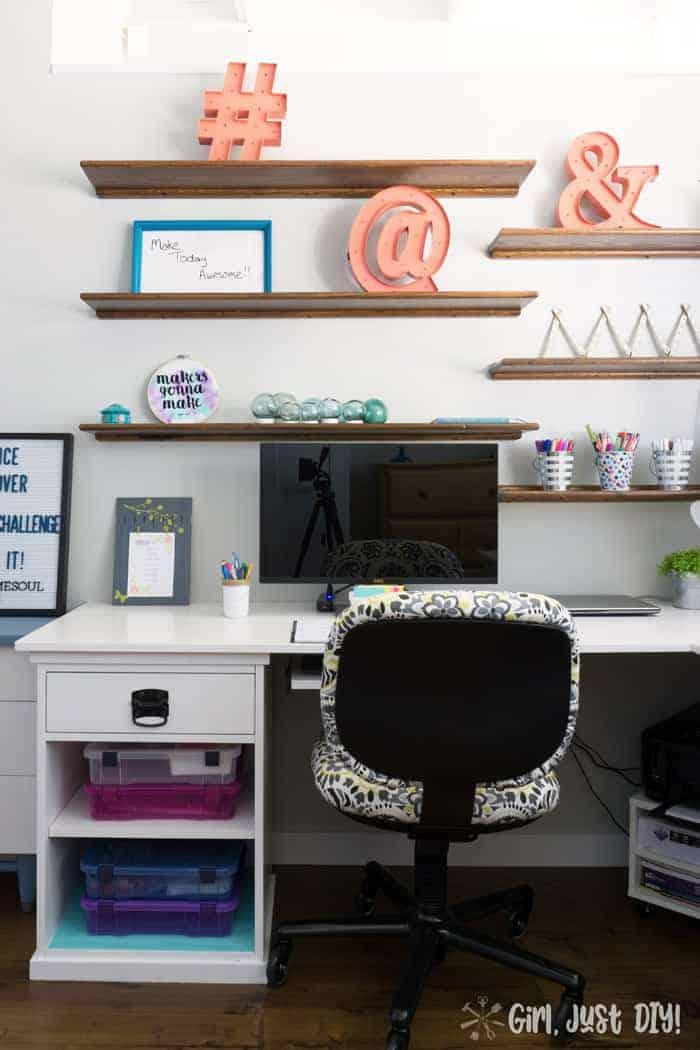 Floating wood shelves over new l-shaped desk in office.