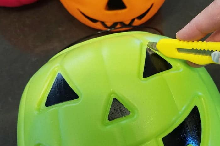 Cutting out eyes of light up pumpkins