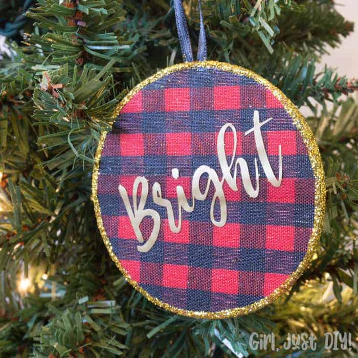 Buffalo plaid christmas ornament with gold glitter trim on lighted tree.