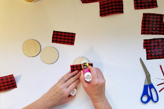 Putting glue stick onto buffalo plaid Christmas ornament round.