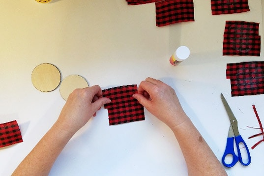 Placing ribbon fabric on buffalo plaid christmas ornament round.