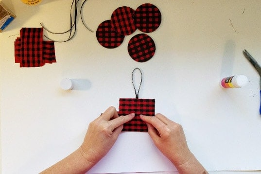 Adding ribbon loop hanger to back of Buffalo plaid ornament.
