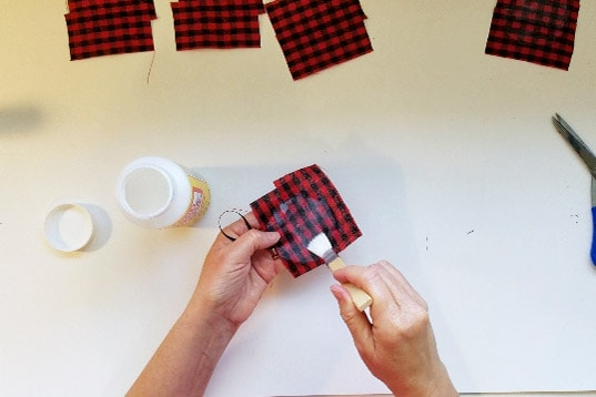 Painting Mod Podge onto fabric of buffalo plaid on ornament.