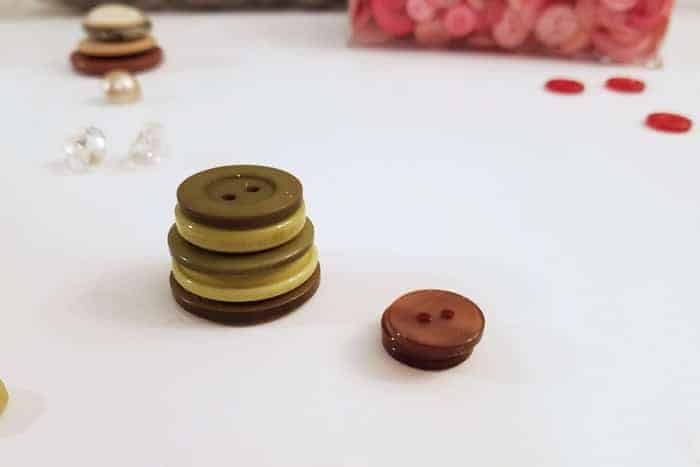 Stacked green buttons making button christmas ornaments.
