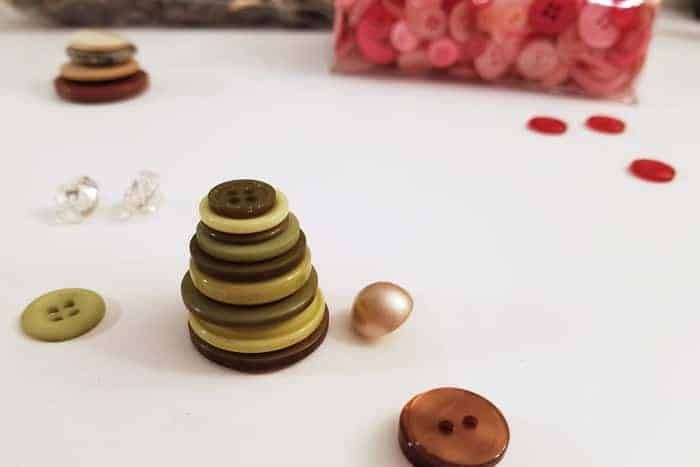 Stacked green buttons on table making button christmas ornaments.
